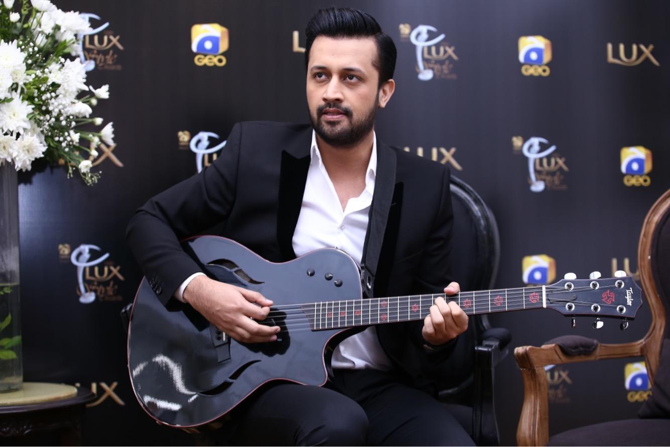 Atif Aslam with guitar in black suit